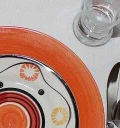 Place setting with orange plate and patterned plate