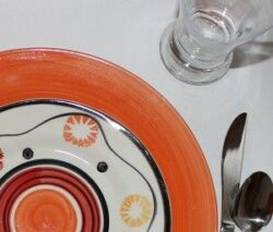 Place setting with orange plate and patterned plate, cropped to top corner