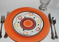 Orange plate topped with patterned plate, with forks, knife, spoon and glass
