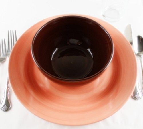 Overhead view of orange plate and brown bowl