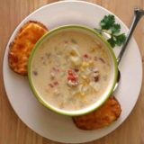Bowl of corn chowder on plate with garlic cheese toast