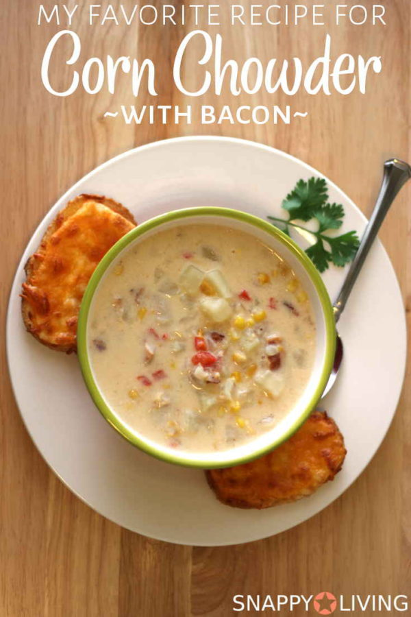 Corn chowder with bacon in a bowl served with garlic cheese bread