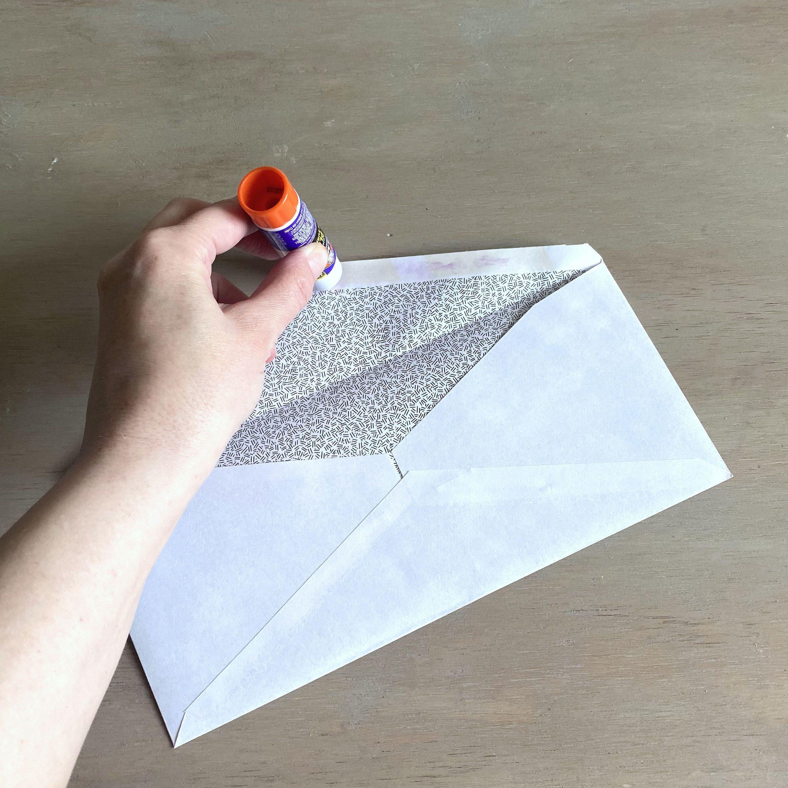 Hand applying glue stick to envelope