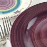 Patterned saucer, purple plate, forks on white surface