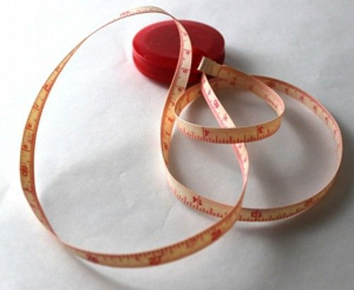 Measuring tape unfurled on white surface