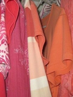 Color-coded clothes hanging in closet
