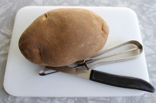 Potato with peeling tool on cutting board