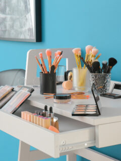 Cosmetics laying on white table with open drawer