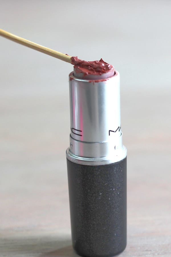 Using a toothpick to get lipstick out of a tube