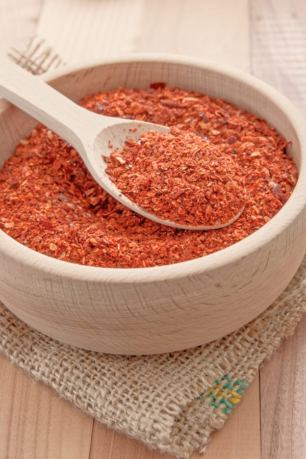 Crushed cayenne pepper in bowl with spoon