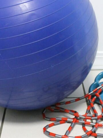 Exercise ball next to jump rope on tiled floor