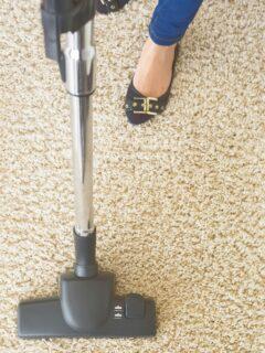 Vacuum on carpet near woman's feet