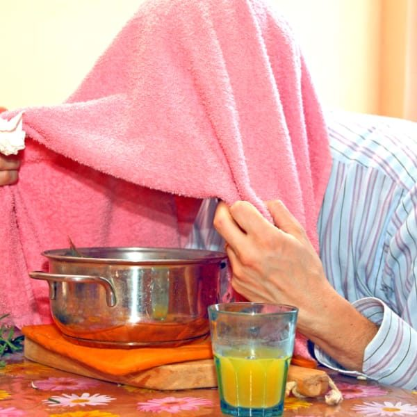 Person with towel over head breathing steam from boiling pot of water