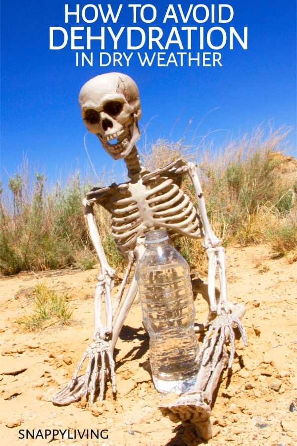 Skeleton sitting in desert with bottle of water