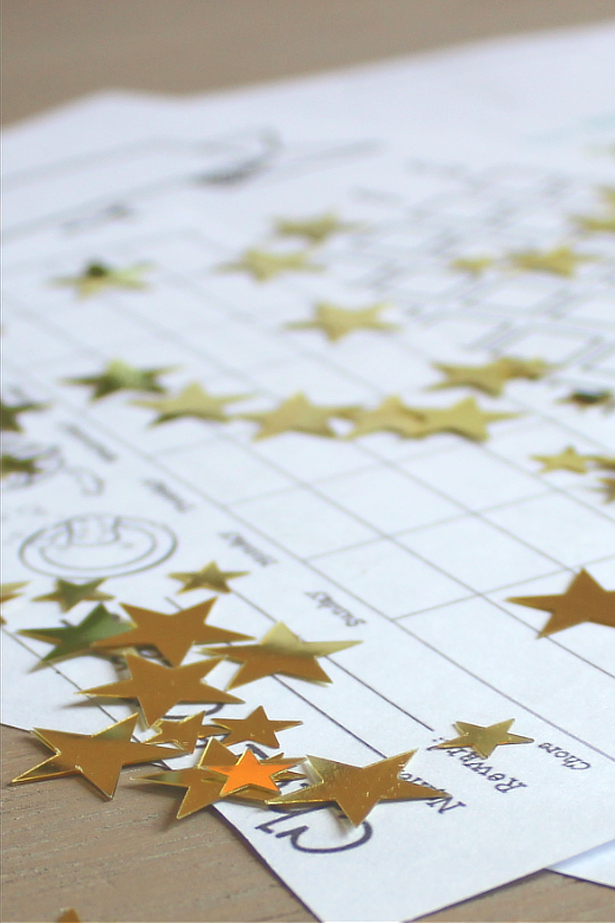 Chore charts on table with gold star stickers scattered around