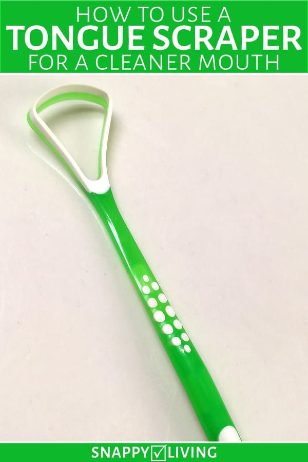Green plastic tongue scraper on white surface