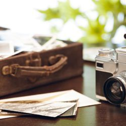 Old briefcase full of photos with vintage camera