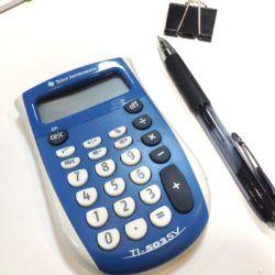 Calculator, pen and binder clip on desk