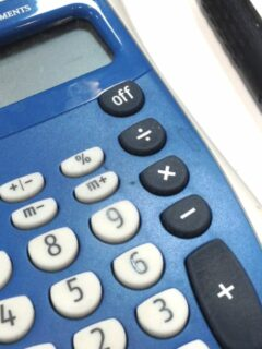 Calculator and other office supplies on white desk surface