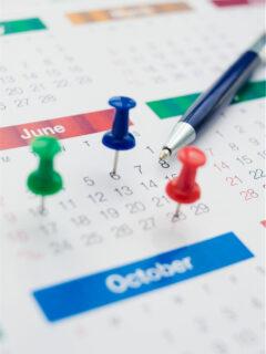 Calendar with thumbtacks and a pen