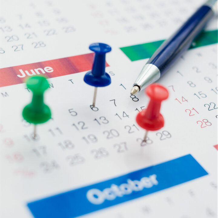 Calendar with thumbtacks and a pen
