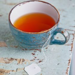 Cup of tea with teabag on blue background