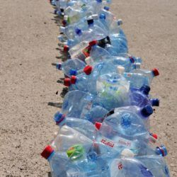 Long line of water bottles in trash