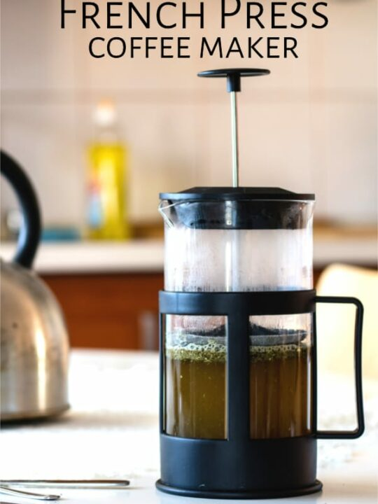 French press full of coffee sitting on a kitchen table