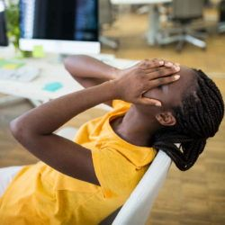 Young woman in an office covering her face with her hands in frustration