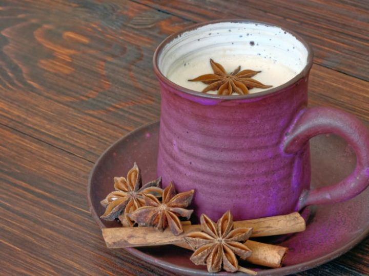 Cup of chai latte garnished with anise star