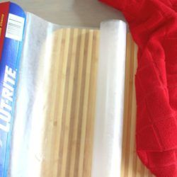 Wax paper on a cutting board by a red dish towel