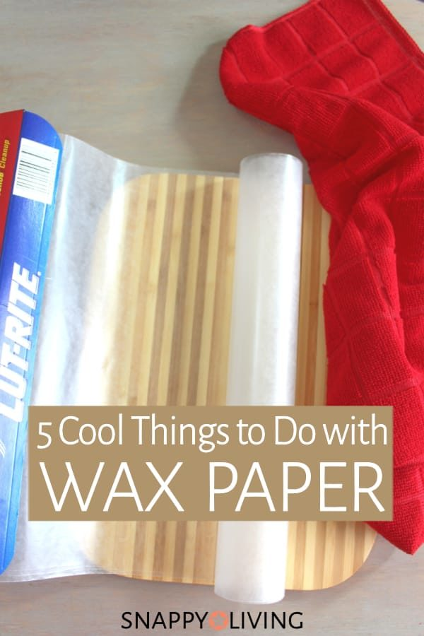 Wax paper on table by cutting board and red dish towel
