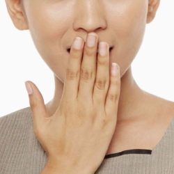 Woman covering mouth after hiccup