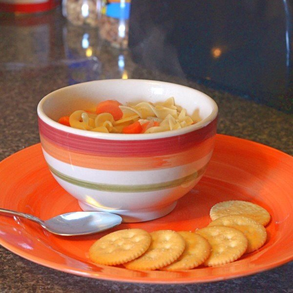 Chicken noodle soup in bowl with crackers