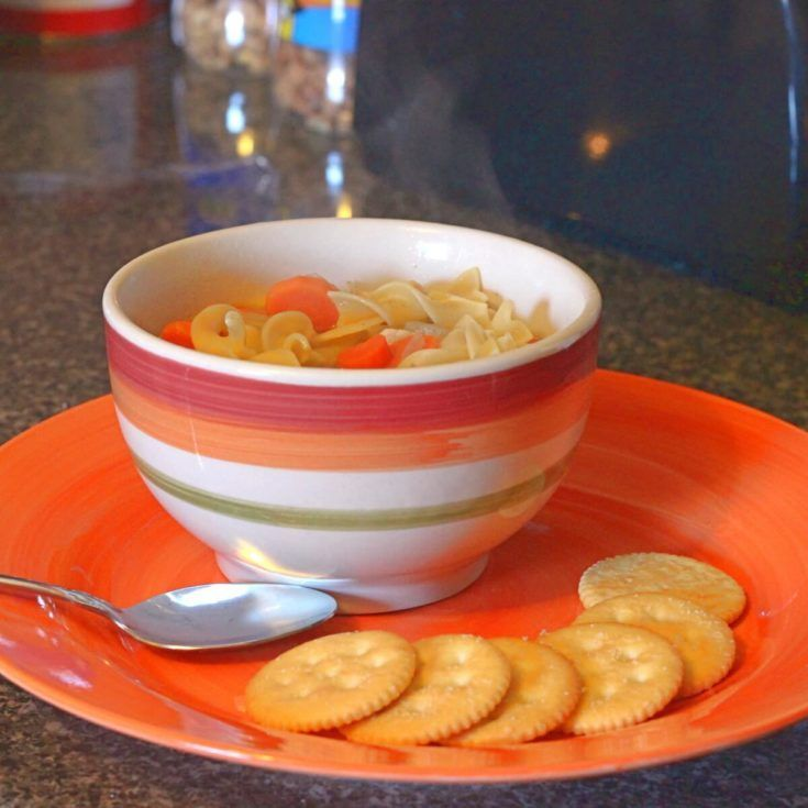 Bowl of chicken noodle soup on orange plate with crackers