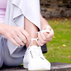 Woman lacing her tennis shoe in park