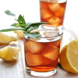 Two glasses of iced tea with mint sprigs on table with lemon wedges