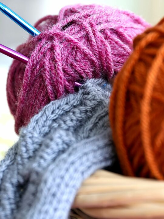 Basket of yarn with knitting needles and knitted scarf