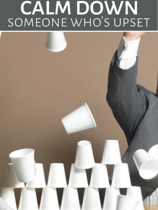 Upset man knocking down stack of cups