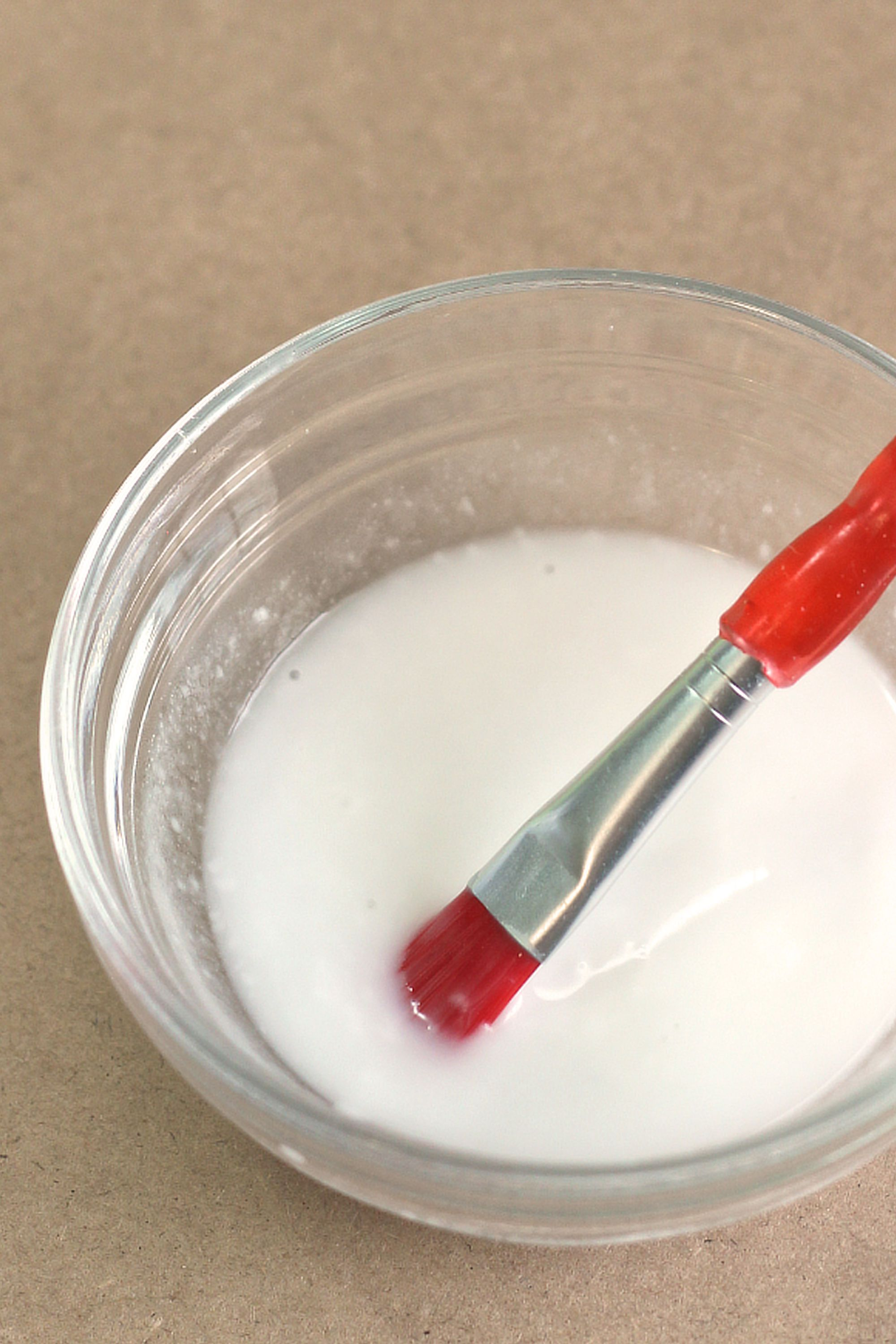 Homemade glue in clear bowl with paintbrush