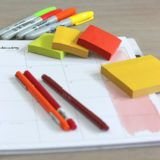 Planner open on desk with colored pens, highlighters and sticky note pads