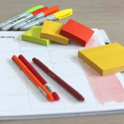 Planner, sticky notes and pens on desk