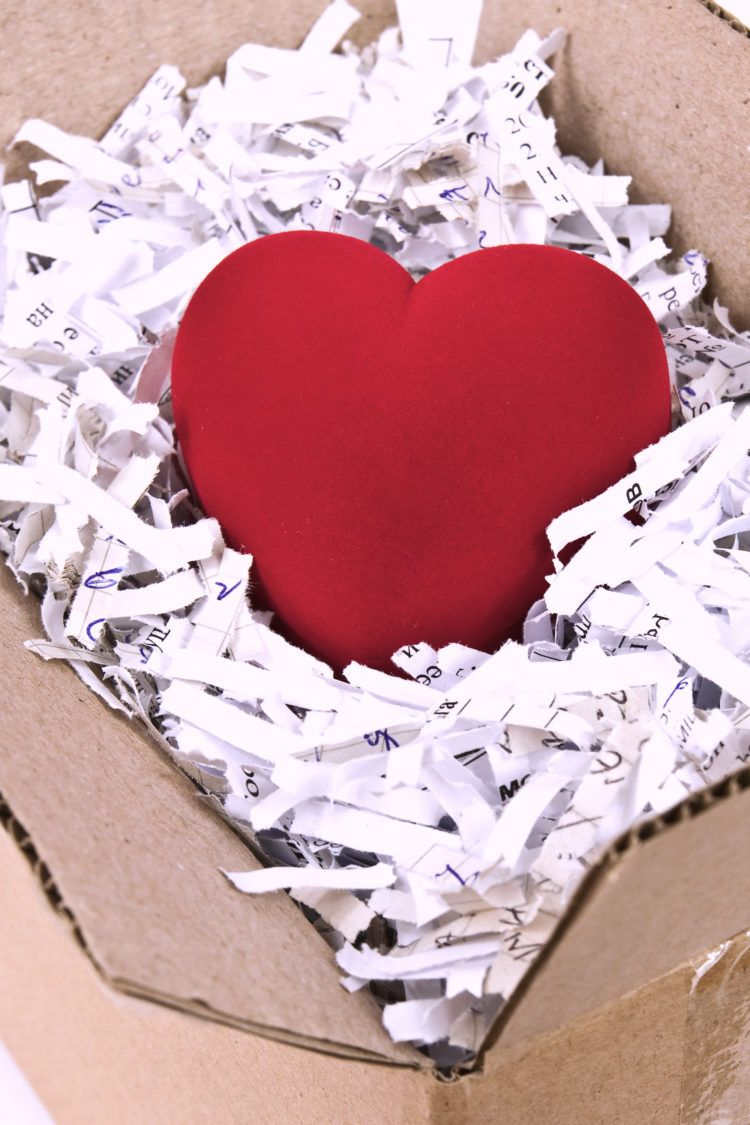 Red plush heart in an open cardboard box with shredded paper around it