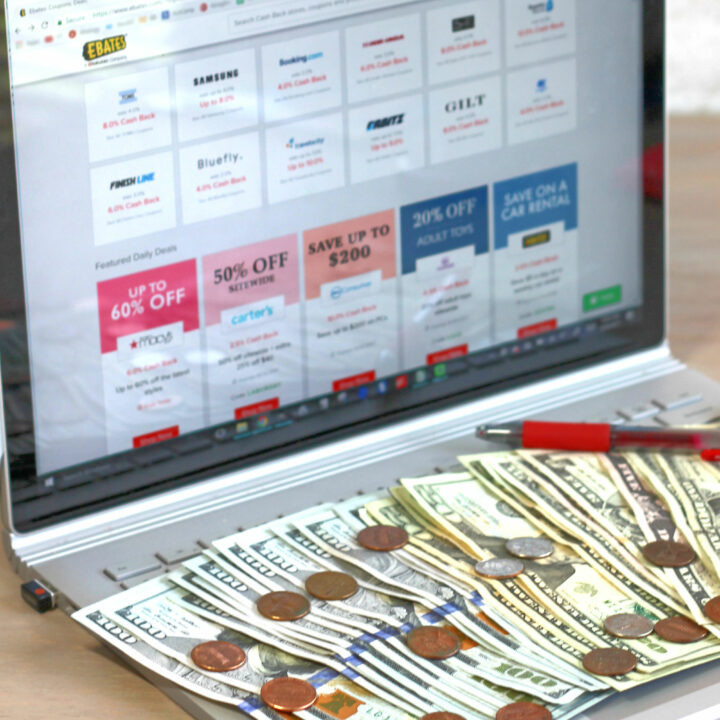 Laptop showing Rakuten cash back website with money on keyboard