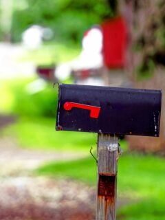 Black mailbox with red flag on rural road