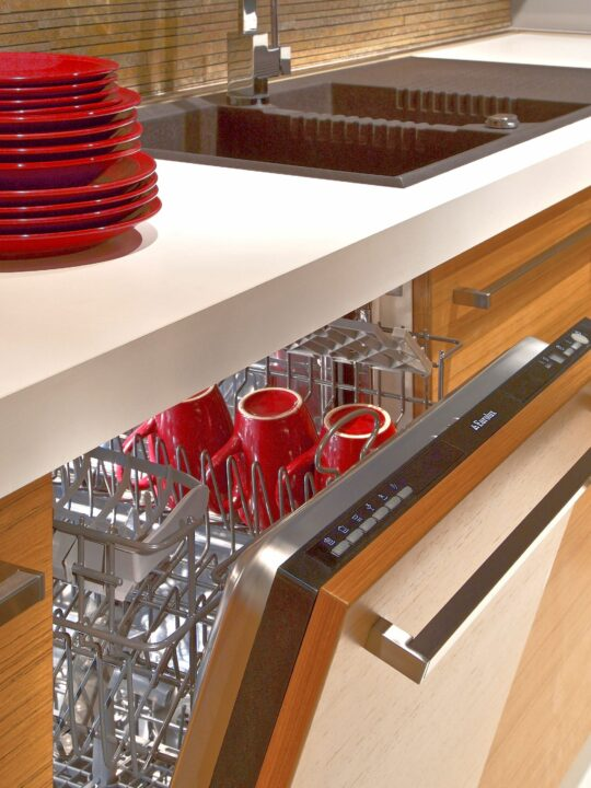 Slightly open dishwasher in kitchen