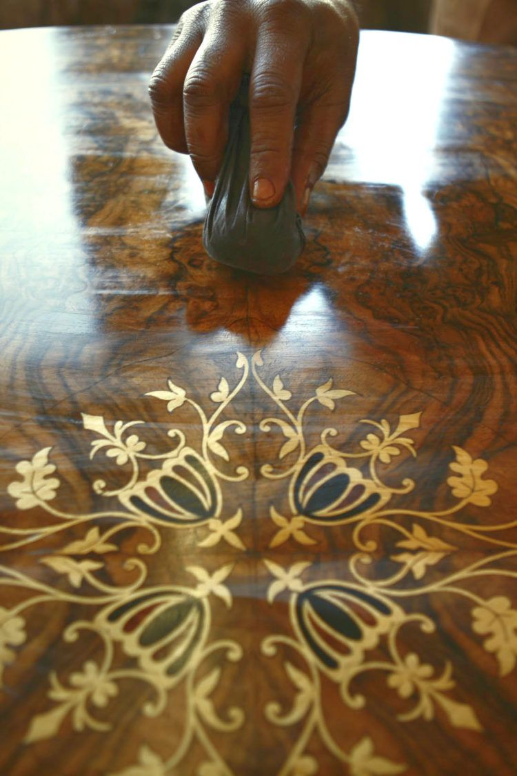Hand polishing ornate table with homemade furniture polish