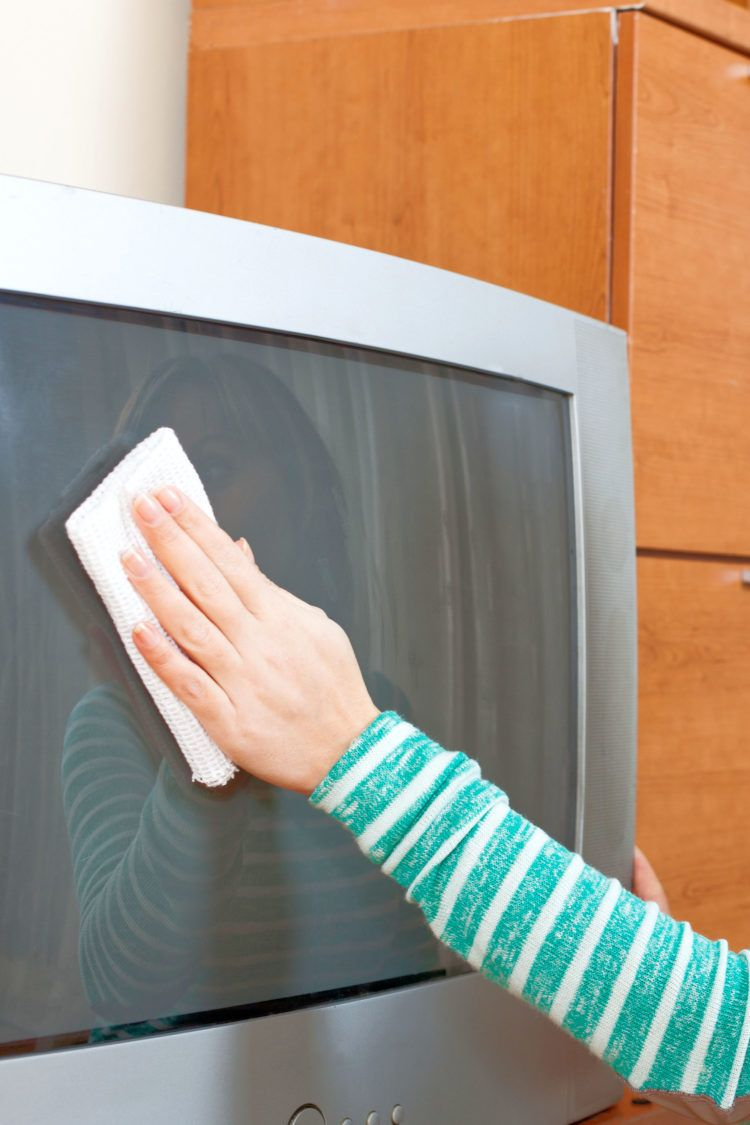 Woman dusting TV screen with used dryer sheets