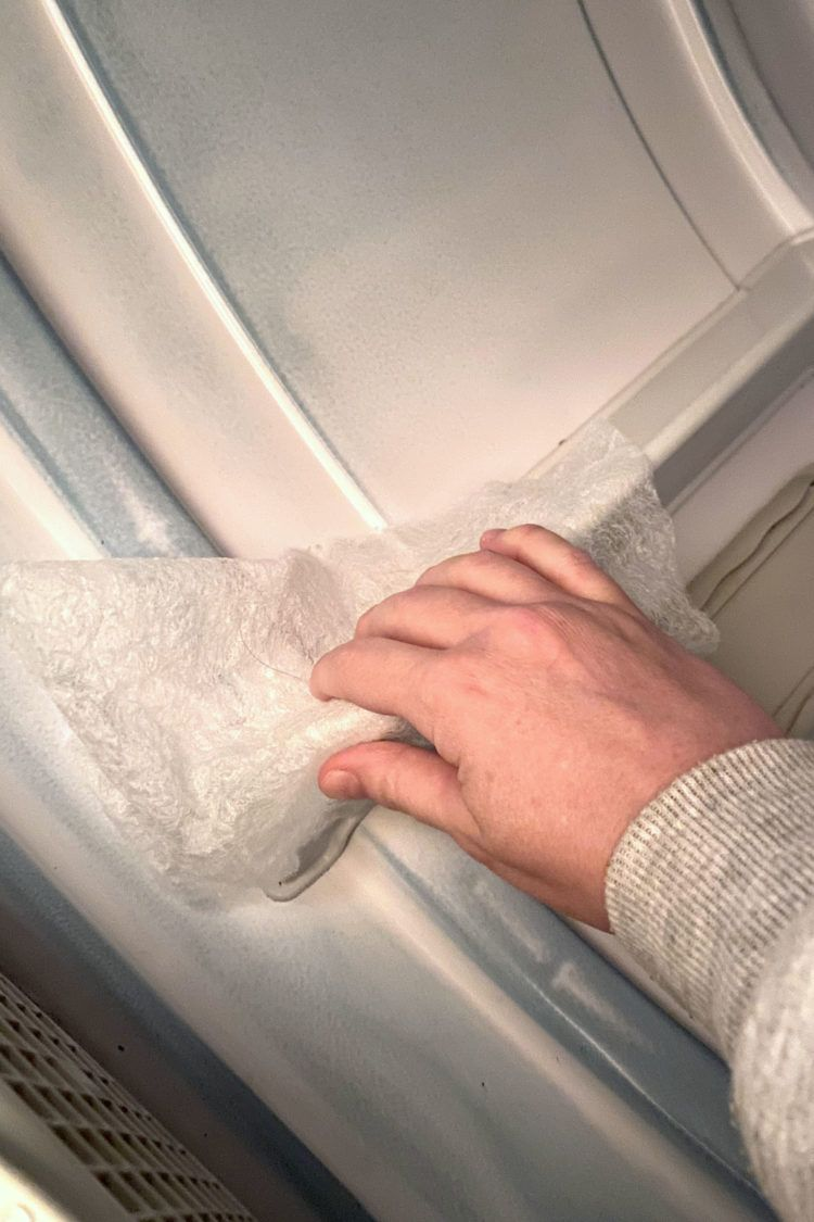 Hand using used dryer sheet to clean inside of a dryer