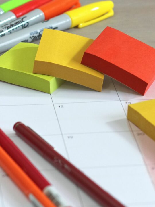 Planner with sticky notes and pens on desk